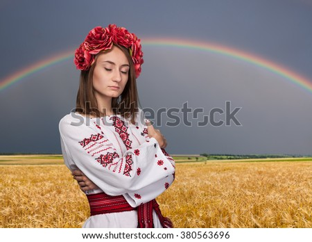 Beautiful young girl in the Ukrainian national suit with closed eyes against wheat field with rainbow
