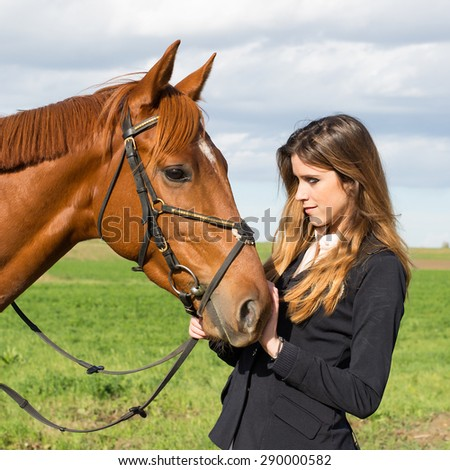 Beautiful young girl in uniform competition hugs her horse : outdoors portrait on sunny day