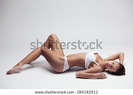 beautiful young girl in white lingerie lying on a light background - stock photo
