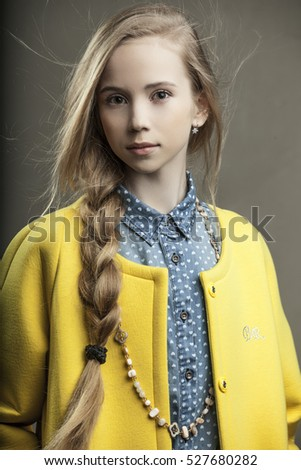 beautiful young girl in yellow coat with bead