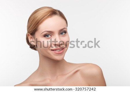 Beautiful young girl is caring of her skin. She is standing and looking forward with joy. The lady with naked shoulders is smiling. Isolated on background - stock photo