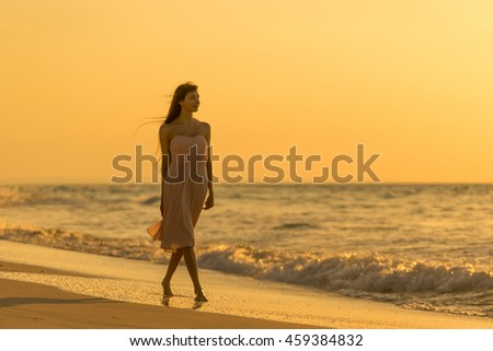 Beautiful young girl is walking on the beach at sunset