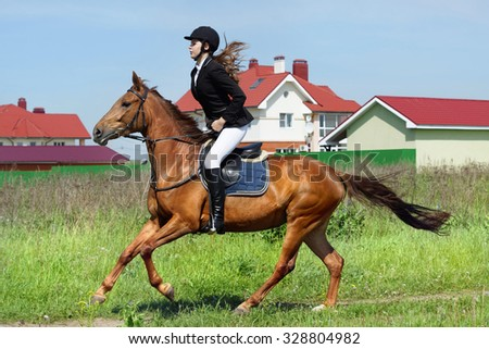Beautiful young girl jockey ridding horse in a field - stock photo