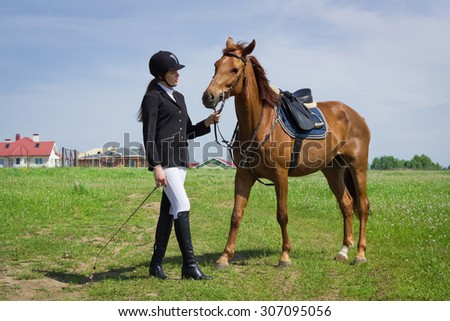 Beautiful young girl jockey talks with her horse dressing uniform competition - stock photo