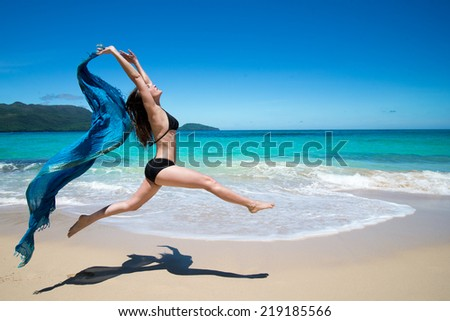 Beautiful young girl jumping with waving blue cape, scarf, on tropical beach in summer