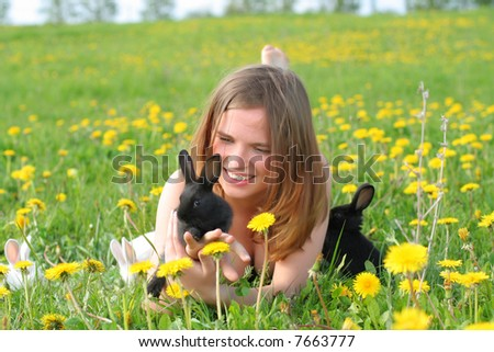 Beautiful young girl lays in grass and plays with cute small rabbits - stock photo