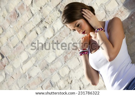Beautiful young girl leaning against the wall of brick - stock photo