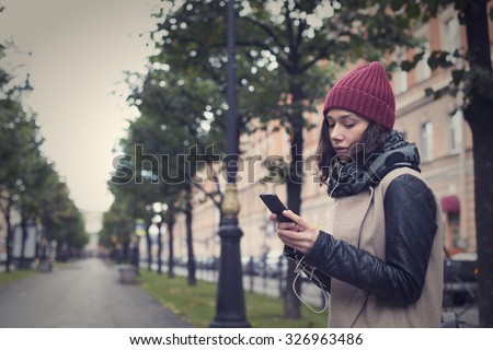 Beautiful young girl listens to music, reads and writes in the smart phone in the center of St. Petersburg - stock photo