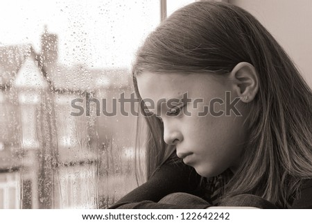 Beautiful young girl looking emptily out of the window