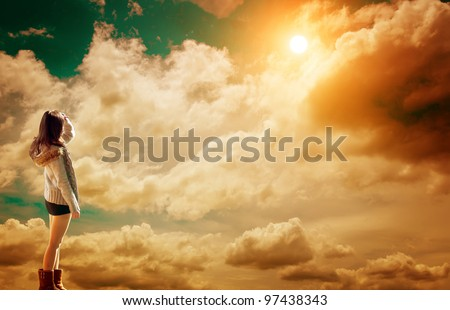 Beautiful young girl looking up at the sky, enjoying the warm sunshine - stock photo