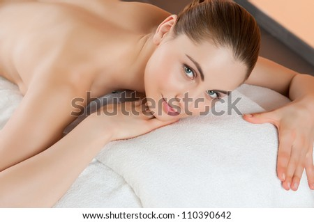 Beautiful young girl lying and relaxing at health spa club