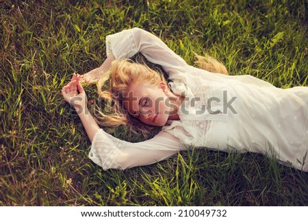 beautiful young girl lying on the grass dreaming - stock photo