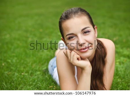 Beautiful young girl lying on the grass in summer park
