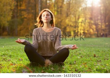 Beautiful young girl meditating in autumn park - stock photo