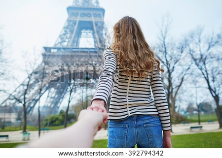 Beautiful young girl near the Eiffel tower, follow me concept - stock photo