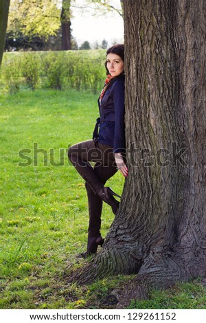 Beautiful young girl near tree in the park