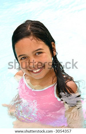 Beautiful young girl of mix parentage enjoying some fun time in the swimming pool. - stock photo