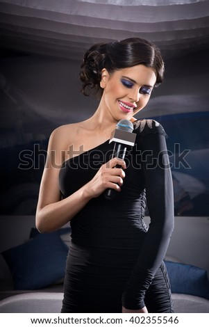 Beautiful young girl on a bright background. Music theme. - stock photo