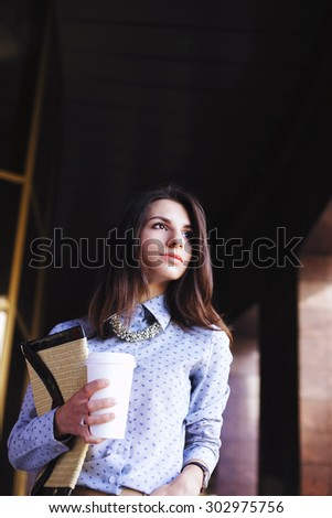 Beautiful young girl on the background of the business center. Office fashion, business fashion. Brunette. Portrait of a young woman. Office worker. Business world. Confident girl. - stock photo