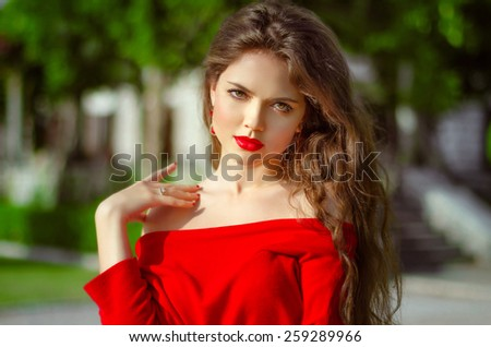 Beautiful young girl Outdoor portrait. Fashion brunette in red dress. Romantic woman posing in green park at sunny day. Fashion photo - stock photo