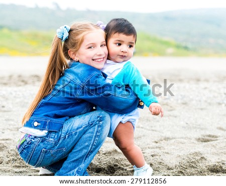 beautiful young girl  playing with a baby  on the beach on a sunny summer day - stock photo