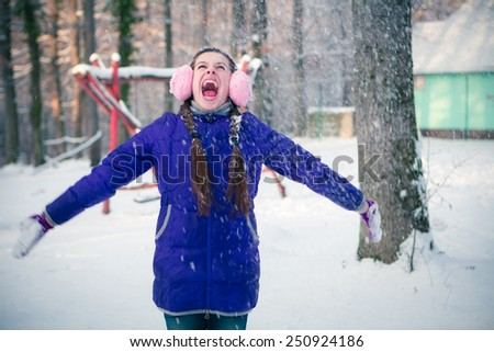 Beautiful young girl playing with snow in motion  - stock photo
