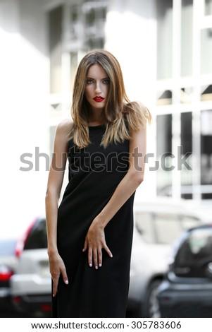 Beautiful young girl posing on city street - stock photo