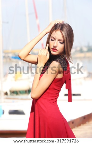 Beautiful young girl posing on river background - stock photo