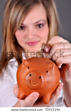 Beautiful young girl putting money in her piggy bank - stock photo