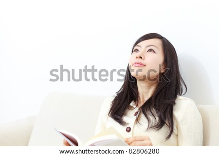 beautiful young girl reading book on a sofa - stock photo