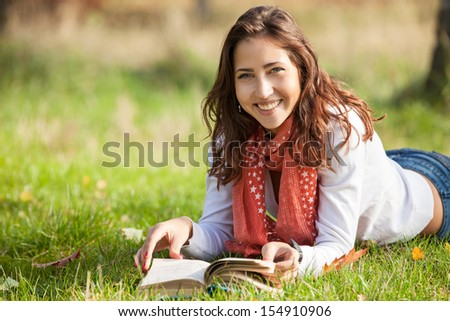 Beautiful young girl reading book while lying on grass  - stock photo