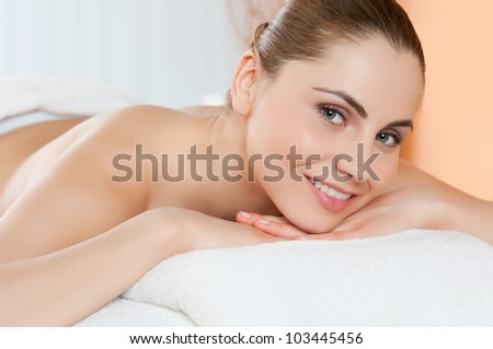 Beautiful young girl relaxing and smiling at camera at spa club