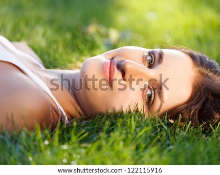 Beautiful young girl relaxing on green grass in summer park - stock photo
