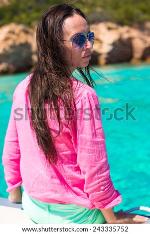 Beautiful young girl relaxing on the boat in open sea - stock photo