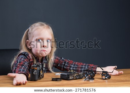 Beautiful young girl repairing a broken vintage film camera - stock photo