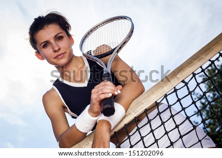 beautiful young girl rests on a tennis net on the sky - stock photo