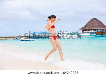 beautiful young girl running along the beach. Velavaru Island Maldives - stock photo