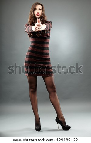 Beautiful young girl shooting with an imaginary gun in full length pose, on gray background - stock photo