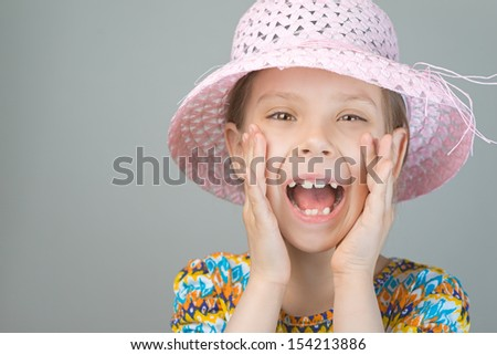 Beautiful young girl shouts loud voice, on gray background. - stock photo