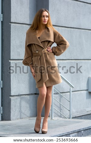 Beautiful young girl showing fashionable brown coat on gray wall background - stock photo