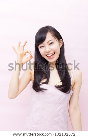 beautiful young girl showing OK sign against pink background
