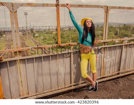 Beautiful young girl sitting behind the metallic lattice