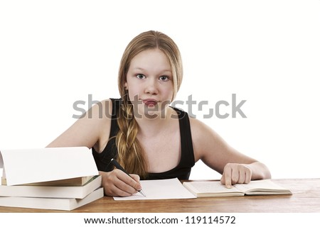 Beautiful young girl sitting by table writing on white background