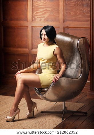 beautiful young girl sitting in a leather chair - stock photo