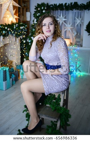 beautiful young girl sitting near the fireplace and Christmas tree