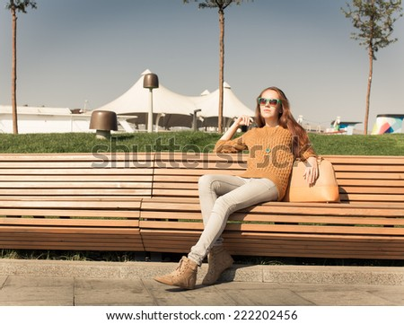beautiful young girl sitting on a bench on a warm summer day