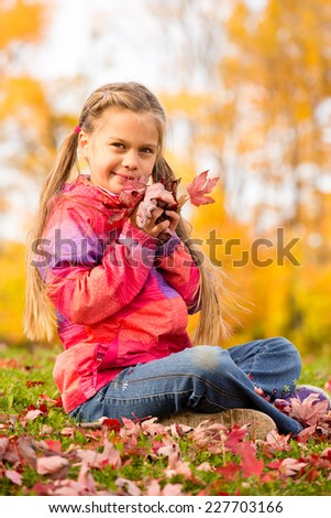 Beautiful young girl sitting on a grass with colorful autumn leaves, holding some red maple leaves close to her face - stock photo