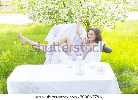 beautiful young girl sitting with cup of coffee and white sweat in park cafe near decor table on green grass and blooming tree background female sit on white armchair Copy space for inscription - stock photo