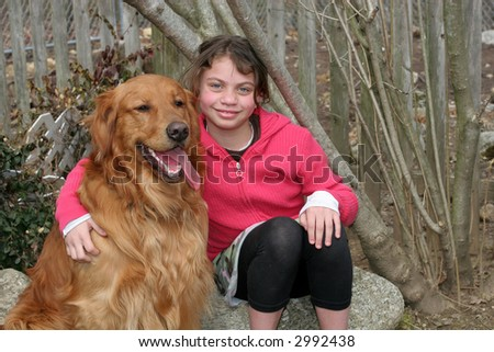 beautiful young girl sitting with golden retriever