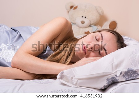 Beautiful young girl sleeping in a bed